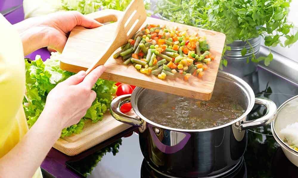 девушка добавляет овощи в суп
